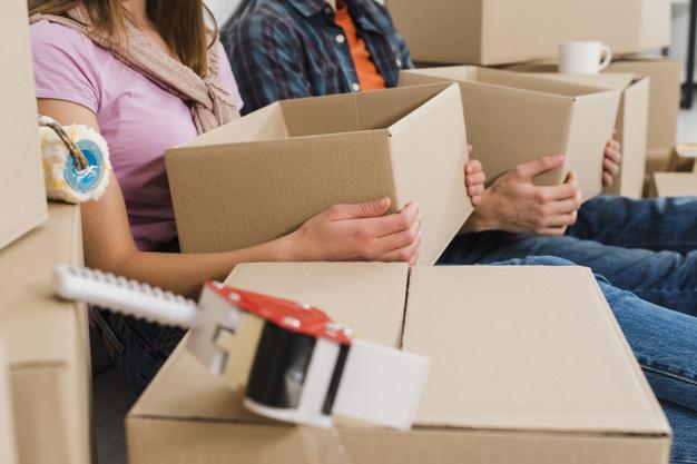 Femme et homme tenant des boîtes en carton.