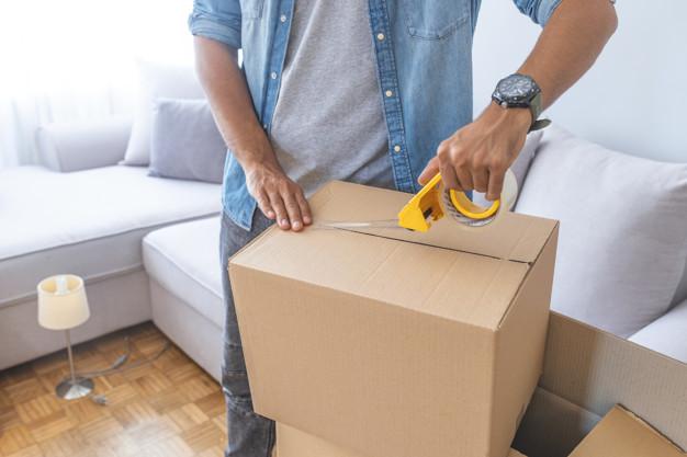 Homme scellant une boîte en carton avec du ruban adhésif.